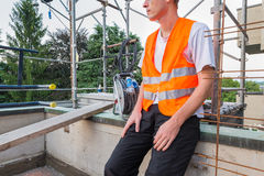 Home repair, building restructuring. Construction worker with reflective safety jacket. Builder, with reflective safety orange jacket, on a terrace - roof for Stock Photo