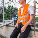 Home repair, building restructuring. Construction worker with reflective safety jacket. Builder, with reflective safety orange jacket, on a terrace - roof for Royalty Free Stock Images