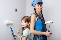 Home repair: mom and daughter make repairs and paint the walls with white paint. stock photos