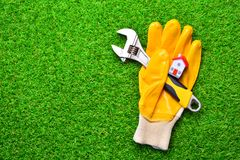 Free Home Repairs Concept. Building Glove With A Adjustable Wrench And Miniature House On A Green Grass. Stock Photos - 134803693