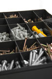 Home repairs kit. Close up of black plastik box with screws and dowels Royalty Free Stock Images