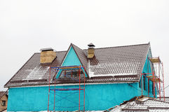 Home repairs outside. Gutter on the roof top of house. Metal roof. Roof Snow Guards. chimney pipe. Royalty Free Stock Images