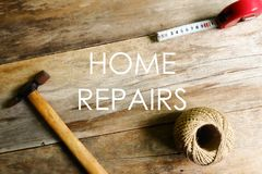 Home repairs written on wooden background with hammer,rope and measuring tape stock photography