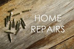 Home repairs written on wooden background with screwdriver stock image
