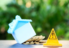 Home, Risky coin stack and Warning label.Financial crisis concep. T.Investing to buy a home is risky Royalty Free Stock Photos