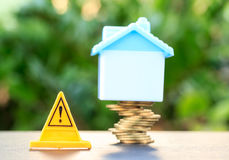 Home, Risky coin stack and Warning label. Financial crisis concept.Investing to buy a home is risky Royalty Free Stock Images