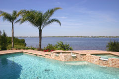 Home on the River. Swimming pool and jucuzzi on the river, with palm trees swaying in the tropic breezes royalty free stock photography