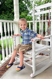 At Home and Rockin. Small boy grins as he sits on a weathered rocking chair on the front porch of his home.  He is wearing flip flops, shorts and short sleeved Stock Photos