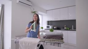 Home routines, cheerful housewife girl is ironing fresh towels and having fun and singing stock footage