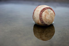 Home run. A baseball lays soaking in the puddle outside the ballpark Royalty Free Stock Photos