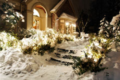 Home's snowy Christmas lights. Outside Christmas lights line path to a front door on a snowy evening royalty free stock photo