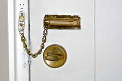 Home Safety. A simple deadbolt and hotel chain-style lock on a white painted door, representing security and safety Stock Photography