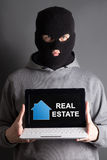 Home safety concept -masked man holding computer with real estat Royalty Free Stock Photos
