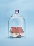 Home safety. A model home protected under a glass dome on blue background Royalty Free Stock Photos