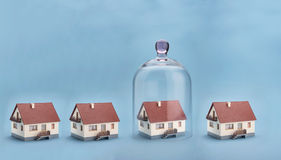 Home safety. A model home protected under a glass dome on blue background Royalty Free Stock Photography