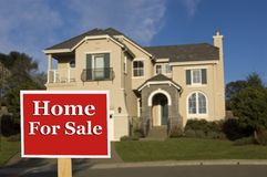 Home for sale. House, slightly soft focus with for sale sign in the foreground Royalty Free Stock Photo