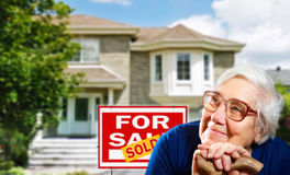 Home for sale and happy senior woman. With glasses Royalty Free Stock Photos
