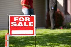 Home: For Sale Sign with Agent and Couple in Back Stock Image