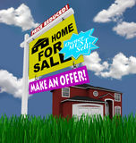 Home for Sale Sign - Desperate to Sell House. A home for sale sign stands in front of a red house, with green grass and blue skies Stock Images