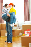 Home for sale sign and guy holding girlfriend Royalty Free Stock Photos