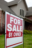 Home with a for sale sign in the yard. A house with a red for sale sign in the yard Royalty Free Stock Photos