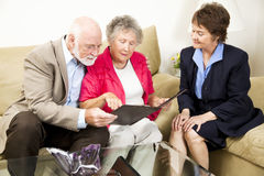 In Home Sales. Sales woman looks on as a senior couple considers her product information Stock Photography