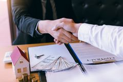 Home sales agents and buyers work on signing new homes and shaking hands stock image