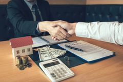 Home sales agents and buyers work on signing new homes and shaking hands royalty free stock images