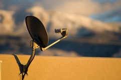 Home Satellite Dish. Mounted to the upper wall of an adobe home illuminated by the warm light of the New Mexico setting sun royalty free stock images