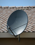 Home Satellite Dish. A new satellite dish mounted on the side of a house Stock Photo