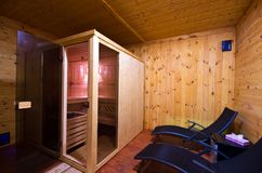 Sauna interior with two sunbeds and cherry wood walls. A home sauna interior with two sunbeds, cabin and cherry color wooden walls Stock Photos