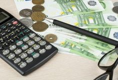 Home savings, budget concept. Calculato,pen, glasses and money on wooden office desk table Stock Photography