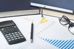 Home savings, budget concept. Chart ,accounting books, pen, calculator and glasses on wooden office table. Chart,accounting books, pen, calculator and glasses Royalty Free Stock Photography