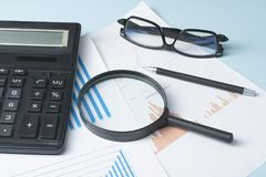 Home savings, budget concept. Chart ,glasses, pen, calculator and magnifying glass on wooden office table. Chart, glasses, pen, calculator and magnifying glass Royalty Free Stock Images