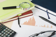 Home savings, budget concept. Chart, notepad, pen, calculator and coins on wooden office desk table. Royalty Free Stock Photo