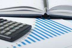 Home savings, budget concept. Chart. pen, calculator and coins on wooden office desk table Stock Photos