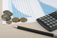 Home savings, budget concept. Chart, pen, calculator and coins on wooden office table.  Royalty Free Stock Photos