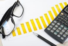 Home savings, budget concept. Chart, pen, calculator and glasses on wooden office desk table. Home savings, budget concept. Chart, pen, calculator and glasses on Stock Images