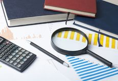 Home savings, budget concept. Chart , pen, calculator and magnifying glass on wooden office table. Chart, notepad, pen, calculator and magnifying glass on Royalty Free Stock Image