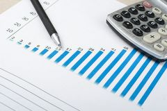 Home savings, budget concept. Chart, pen and calculator on wooden office desk table. Home savings, budget concept. Chart, pen and calculator on wooden table Royalty Free Stock Images
