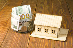 Home savings, budget concept. Model house and coins on wooden office desk table. Stock Photography
