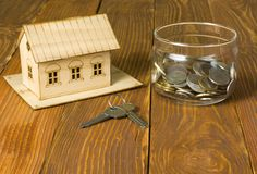Home savings, budget concept. Model house,keys and coins in glass jar on wooden background. stock photography