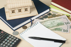 Home savings, budget concept. Model house, notepad, pen, calculator and coins on wooden office desk table. Stock Image