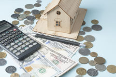 Home savings, budget concept. Model house, notepad, pen, calculator and coins on wooden office desk table. Stock Photos