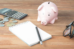 Home savings, budget concept. Model house, notepad, pen, calculator and coins on wooden office desk table. Royalty Free Stock Photos