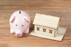 Home savings, budget concept. Model house, notepad, pen, calculator and coins on wooden office desk table. Stock Photo