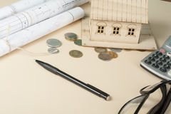Home savings, budget concept. Model house, notepad, pen, calculator and coins on wooden office desk table. Royalty Free Stock Photography