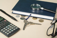 Home savings, budget concept. Model house, notepad, pen, calculator and coins on wooden office desk table. Stock Images