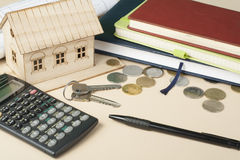 Home savings, budget concept. Model house, notepad, pen, calculator and coins on wooden office desk table. Royalty Free Stock Photo