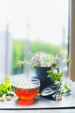 Home scene with Cup of hot herbal tea on window still at nature background, vertical. Stock Images